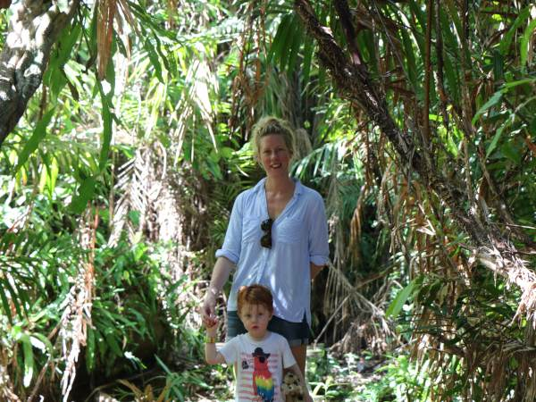 Woman and son smiling amongst jungle