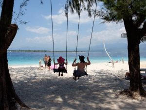 Family swinging on white sandy beach