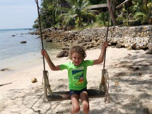 Young boy swinging on swing at beach