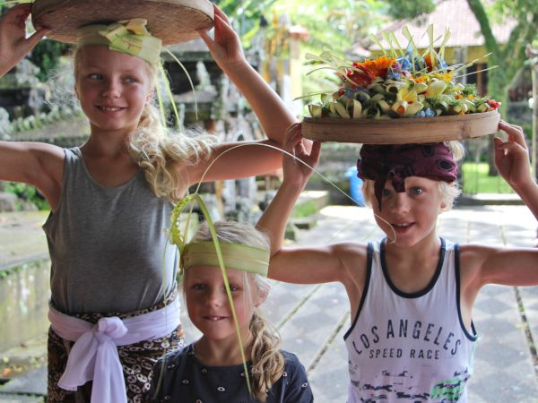 Three children with basket of flowers on head