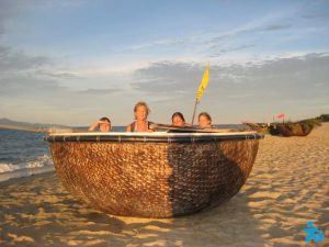 Family sitting in boat on beach