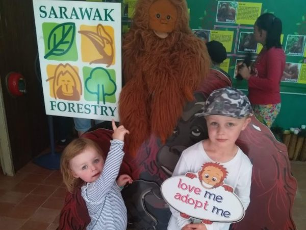 children posing with sign in semenggoh, Borneo