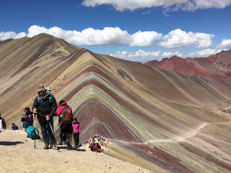 Hikers standing in front of rainbow mountains in peru