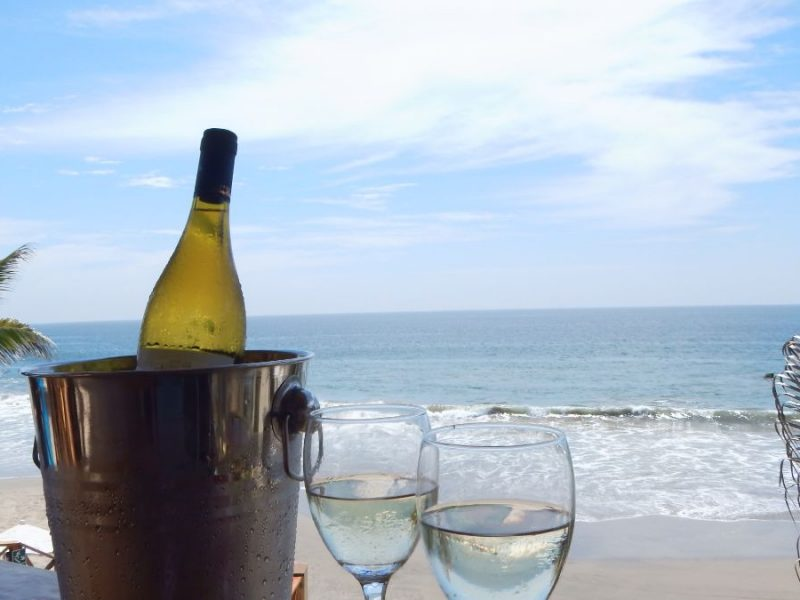 Peru Mancora beach with the sea and a bottle of bubbles with two glasses