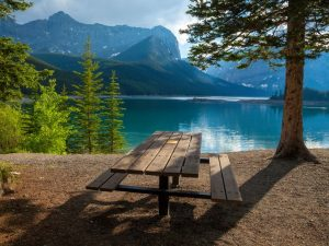 Picnic bench next to ice blue lake