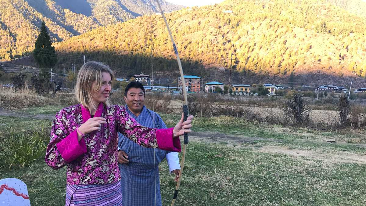 travel specialist kate learning archery in bhutan
