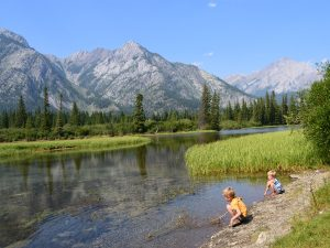Two boys sitting on side of lake