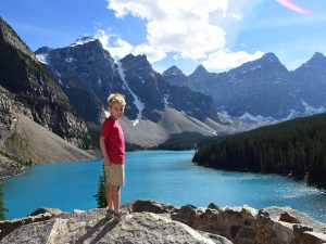 Boy standing on rocks in front of ice blue water