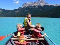 Mother and sons rowing canoe on ice clue lake