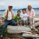 old couple with grandsons sitting on log