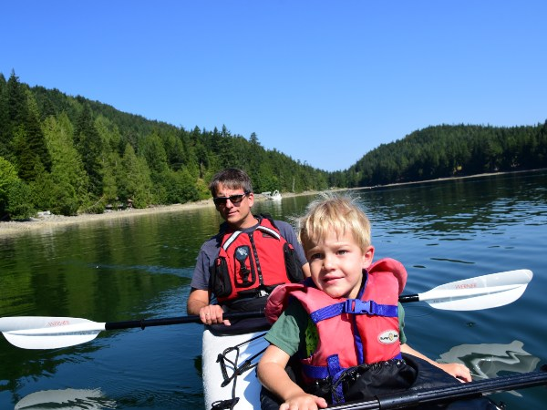 Boy and man sitting in kayak on lake