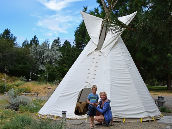 Family sitting infront of Tipi