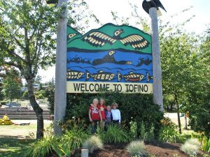 Four girls standing next to sign that reads welcome to Tofino