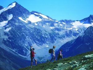 Family walking on grassy hill with snowy mountain behind
