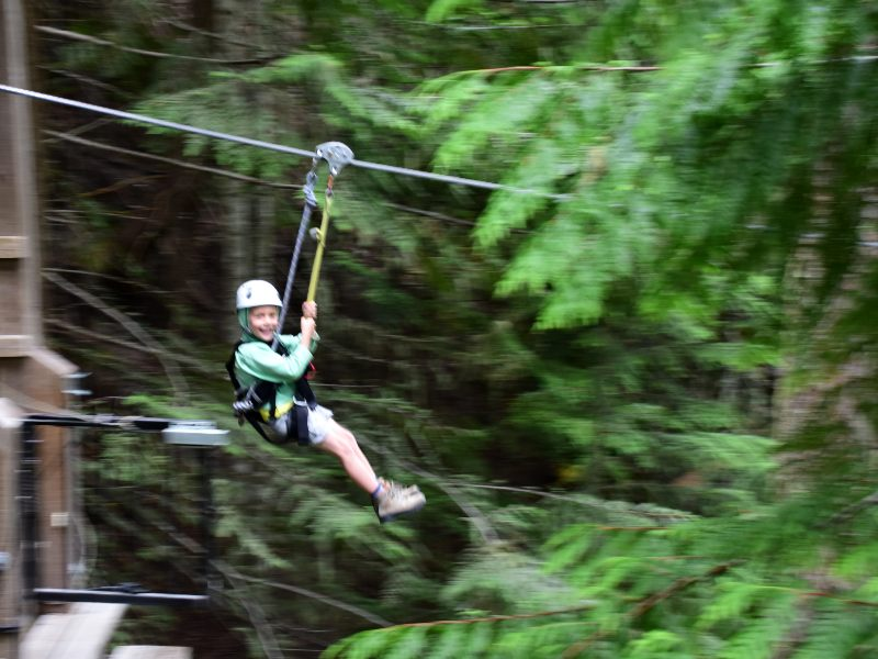 Boy ziplining through trees