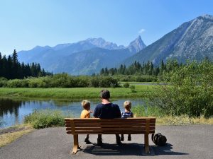 father and son sitting on bench in front of mountain landscape