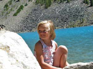 young girl sitting on rock in front of ice clue water