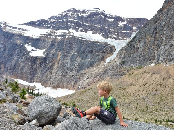 young boy perching on snowy peaked mountains