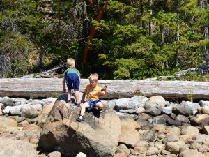 Two young boys playing on rocks
