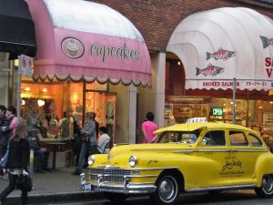 Bright yellow taxi outside cupcake store