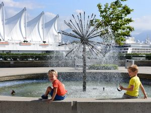 Two young boys sitting by fountain