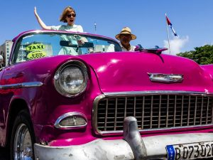 Woman standing up posing in pink classic car