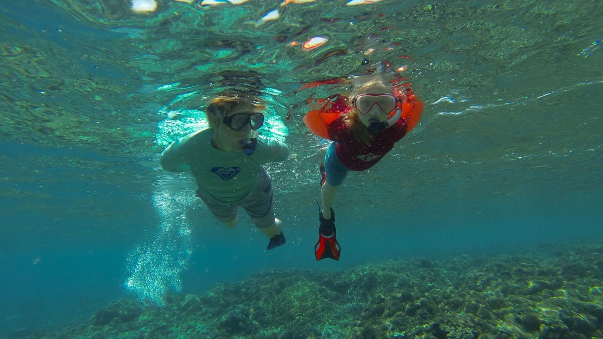 family snorkelling in the sea