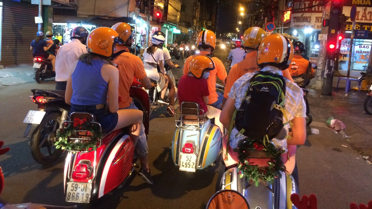 family riding through the streets of saigon on vintage vespas at night
