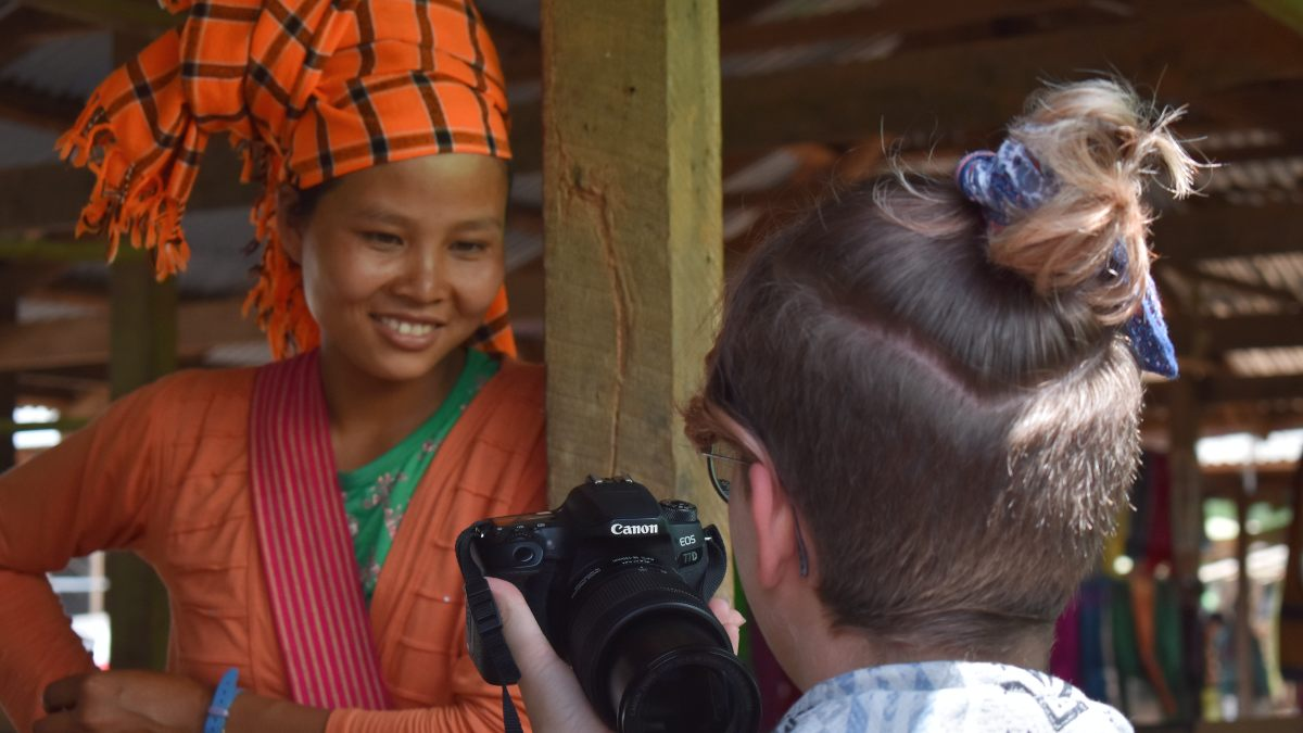 burmese woman looking at photograph with traveller