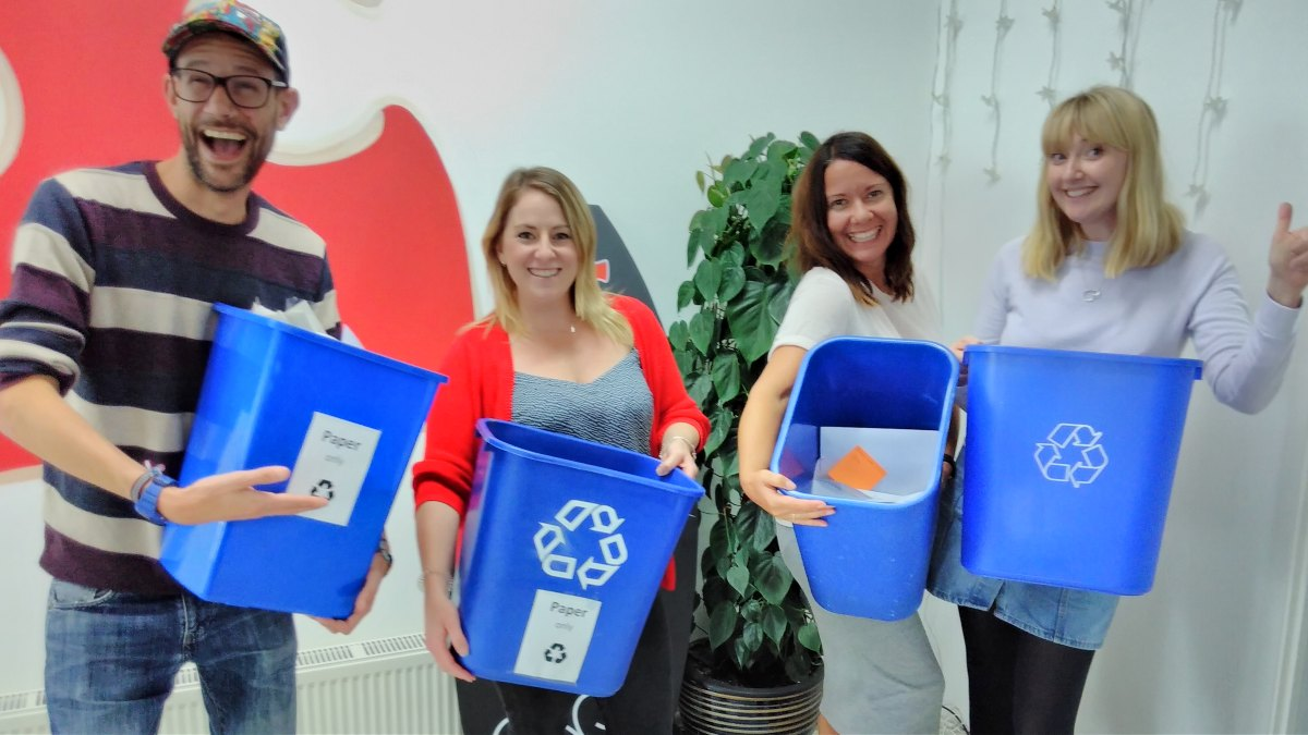 Group of people holding recycling bins