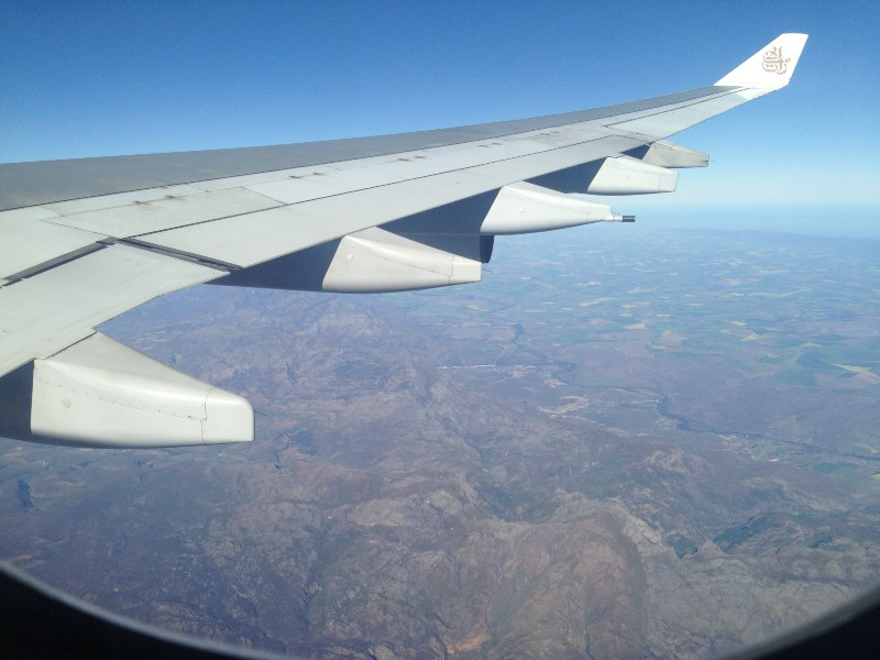 Wing of plane over country