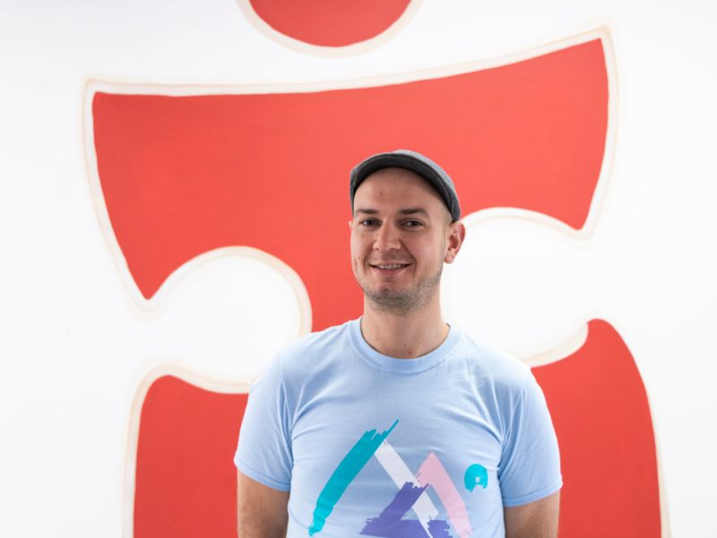 Man in glat cap in front of red puzzle piece