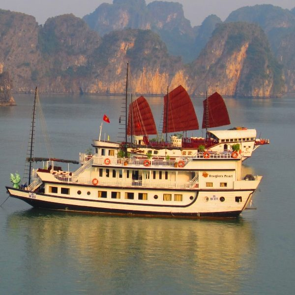 traditional chinese junk boat sailing through limestone islands