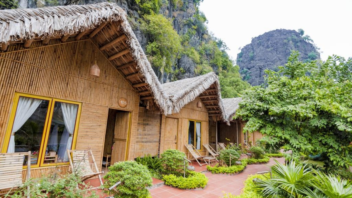 thatched bungalows by jungle clad mountain