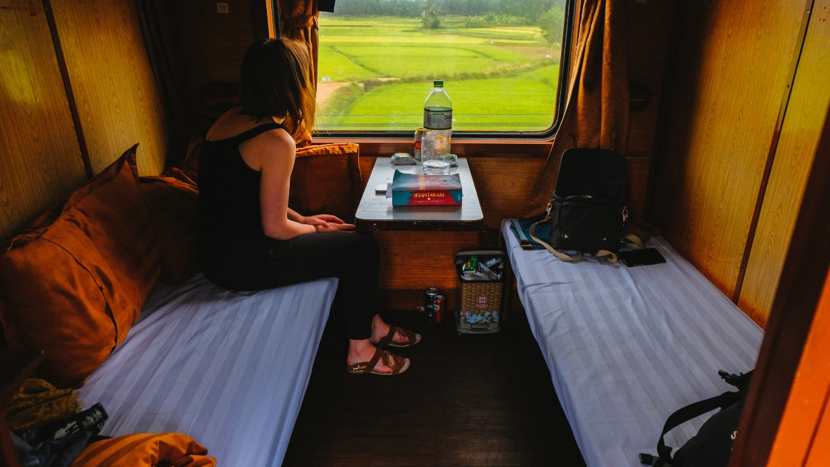 woman looking out of window at rice fields on train in vietnam