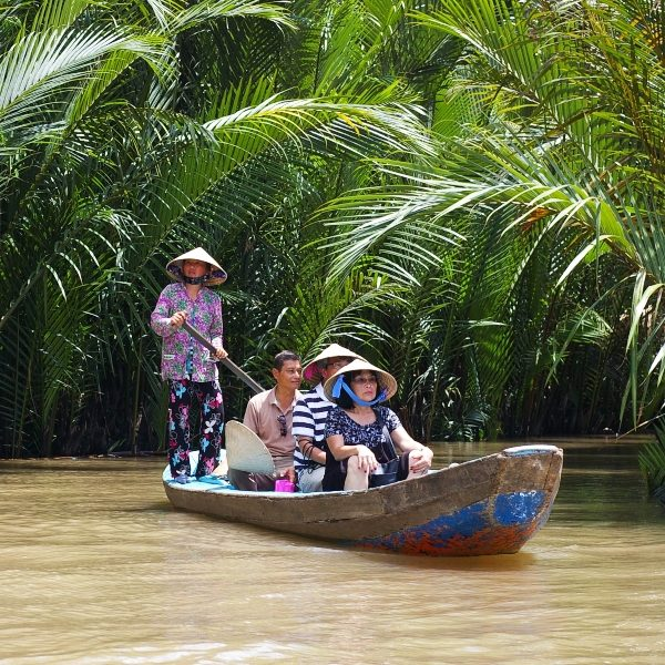 group of tourists on boat being paddled along by local woman on the river in the mekong delta