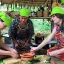 travellers cooking thai food with local woman