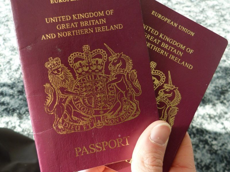 person holding two passports