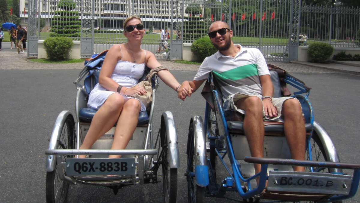 couple holding hands whilst sat in rickshaw cyclos outside palace gates
