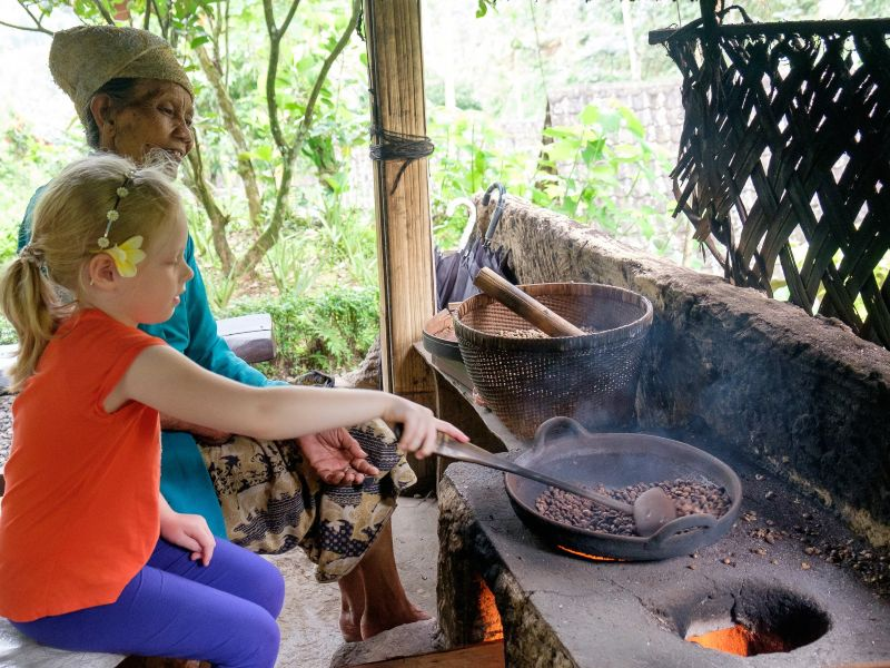 Young girl roasting coffee beans with local lady