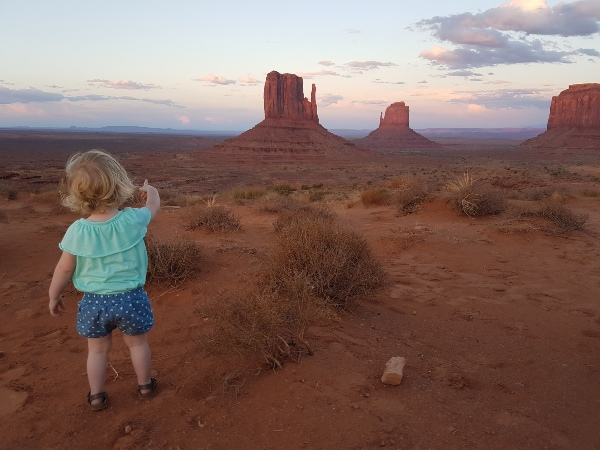 child pointing out at view of sandy rocks