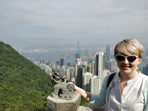 woman standing on viewpoint in front of hong kong buildings