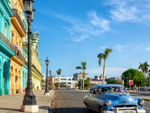classic car outside colourful buildings in havana