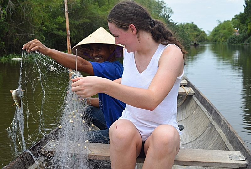 teenage girl fishing on a vietnam boat with a local