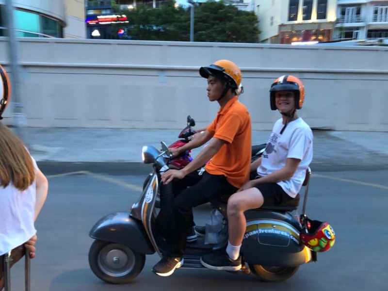 Local and a teenager on moped through Vietnam