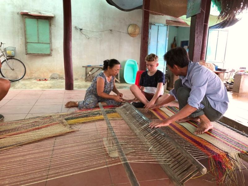 two local people weaving a mat with a young boy