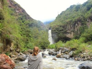 Woman looking at waterfall in Banos, Ecuador