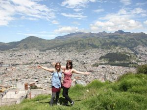 Two women in front of view of Quito