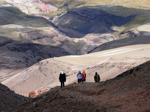 people hiking up mountain in cotopaxi
