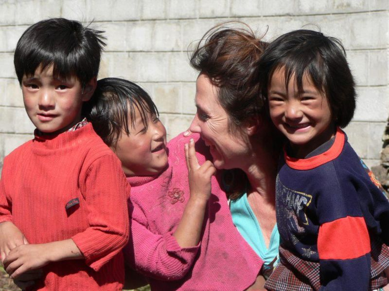 happy children in bhutan with tourist lady